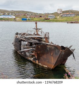 Rotting, abandoned ship on a water of sea bay against the background of an abandoned village, symbols of decadence and degradation
