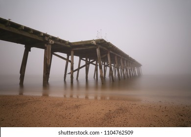 The rotting timbers of the pier and groyne on Lowestoft beach in Suffolk, England on a misty, foggy day