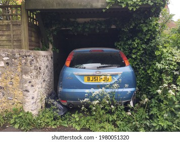 Rottingdean UK - May 24 2021 selective focused photo of unused blue car parked in outdoor garage with overgrown weeds indicating that it is unused for a long time during coronavirus pandemic lockdown