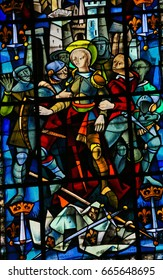 ROUEN, FRANCE - FEBRUARY 10, 2013: Joan of Arc captured by the Burgundians at the Siege of Compiegne (1430) on a stained glass in the cathedral of Rouen, France