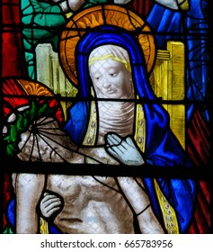 ROUEN, FRANCE - FEBRUARY 10, 2013: Mother Mary mourning with Jesus who died on the Cross, on a stained glass in the cathedral of Rouen, France