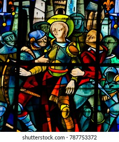 Rouen, France - February 10, 2013: Joan of Arc captured by the Burgundians at the Siege of Compiegne (1430) on a stained glass in the cathedral of Rouen.