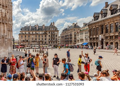 ROUEN, FRANCE - JULY 3RD, 2018. Place du Vieux-Marché, On the left, the Cathedral, a group of adult and adolescent tourists, with far, a small train of walk.