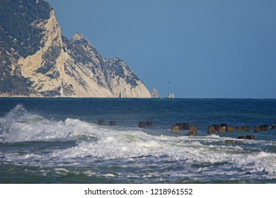 rough Adriatic sea in October in Italy with the cliffs of Monte Conero in the background and two rocks known as the due sorelle or two sisters taken from Porto Recanati near Ancona