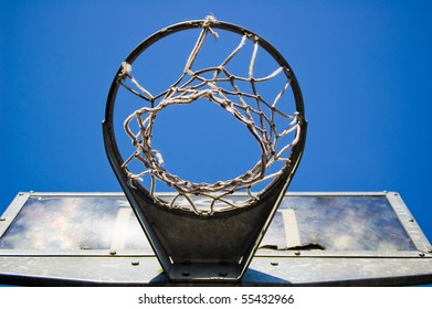 A rough basketball hoop from underneath, with clear blue sky.