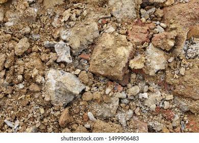 Rough broken concrete and brick, mixed with soil and stones from an excavation - abstract background texture