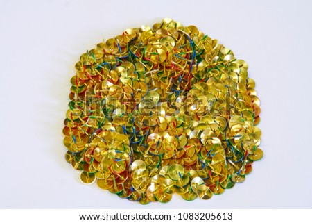 rough circle formed of drawing pins laying on thier heads made up of red, green, blue, white and yellow pins, on a white background