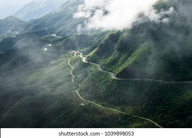 Rough curved road in green valley with foggy
