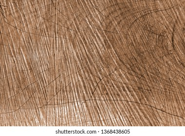 rough cut brown timber surface with patterned scratched surface over the natural grain and crack