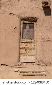 Rough hewn wood door with damaged screen and wooden porch in adobe mud pueblo dwelling in Taos New Mexico