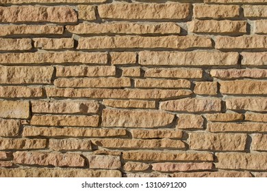 Rough jagged brick stone wall with natural tan color