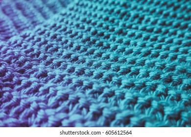 Rough Knitwear, woolen textile texture backdrop, macro. Blue and violet color palette clothes fabric.