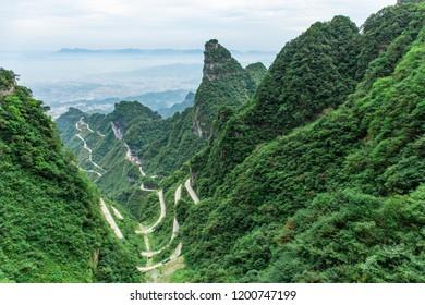 Rough mountain and canyon landscape, curved winding mountain road spiraling up in Tianmen Mountain, Zhangjiajie, Hunan Province, China