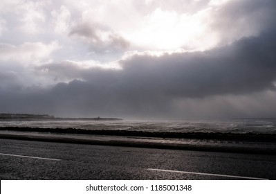 Rough ocean of Galway Bay during Hurricane Ali, with large waves and clouds. Showing Mutton Island in the distance and a road in the foreground