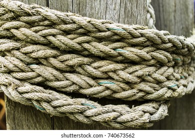 Rough old rope on weathered wood background.