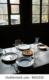 Rough plank dining table set with antique cutlery, plates and glasses.