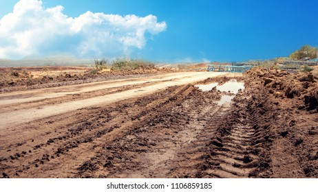 Rough road in the countryside. There are mud basins and wheels.