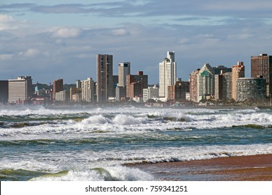 Rough sea against blue cloudy city skyline on Durban Golden Mile beachfront in South Africa