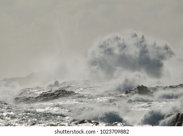 Rough sea on the coast, big wave when breaking and blurred silhouette of lighthouse in the background, Telde, Canary islands