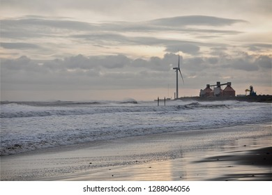 Rough seas at Cambois in Northumberland on the north east coast of England with the storage silos at the mouth of the River Blyth on the horizon together with wind turbines reflected in the wet sand.