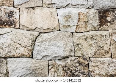 Rough stone, natural texture. Ancient masonry. Wall, fortress, foundation. Gray tones.