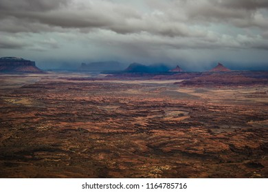 Rough, stormy weather is seen forming over the Needles Overlook in  Canyon Rims Recreational Area near Monticello, Utah. Background fog appears to be at ground level, enveloping the land formations.