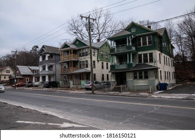 The rough street in the run-down neighborhood with decrepit buildings surrounded by chain-link fences and old cars parked next to it on a gloomy, grey winter day.
