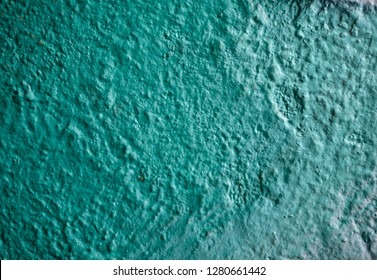 Rough teal colored painted plaster wall for background