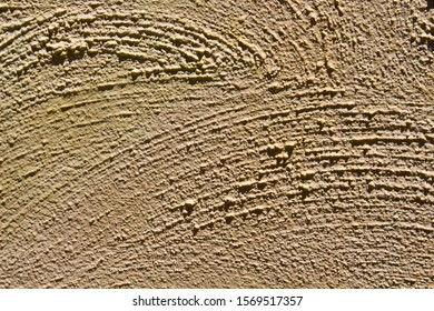 Rough texture of a large light tan colored weathered painted concrete  wall may be ideal for a grungy textured background.