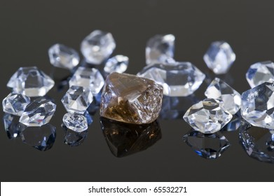 A rough, uncut, brown diamond with quartz rock crystals on a black reflective surface.