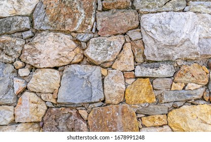 rough various colored stone wall closeup, seamless natural background