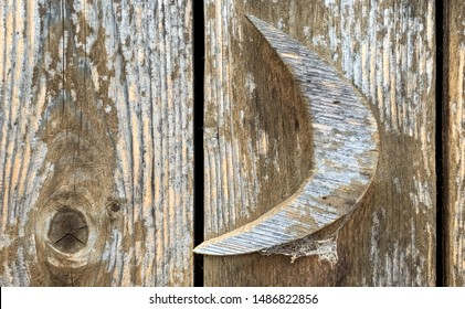 Rough wood and peeling paint on an old wood outhouse, with a cut wood crescent moon on the door.
