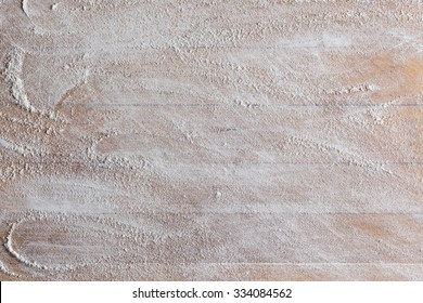 Rough wooden rectangular used cutting board background with flour directly from above closeup