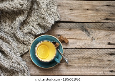 Rough woolen sweater, cup of green tea with lemon and brown sugar on rustic weatheered wood background. Top view point.