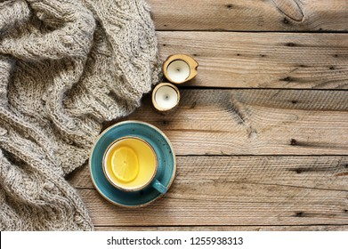 Rough woolen sweater, cup of green tea with lemon and candles on rustic weatheered wood background. Top view point.