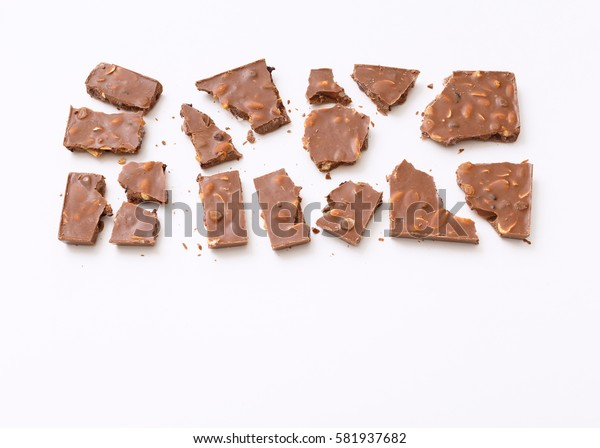 Roughly broken milk chocolate on colorful white background, top view flat lay. Minimal concept above decoration, milk chocolate food background. Chocolate Candy.