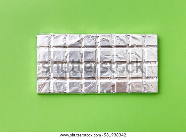 Roughly broken milk chocolate on colorful green background, top view flat lay. Minimal concept above decoration, milk chocolate food background