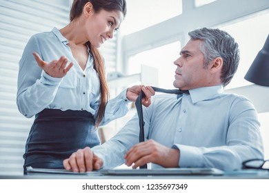 Roughly grabbing tie. Rude good-looking female expressively asking her coworker while holding his tie with her hand