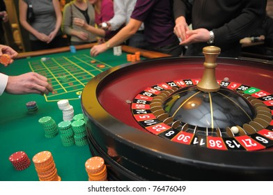Roulette and piles of chips on a green table