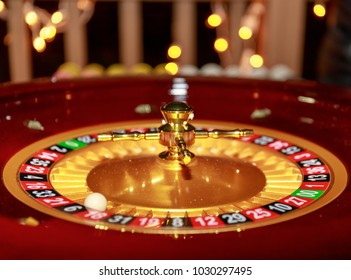 Roulette table in casino. Ball in the rotating gambling machine. Wooden roulette wheel.