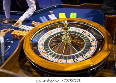 Roulette table in casino. Ball in the rotating gambling machine. Wooden roulette wheel. Casino croupier dealing roulette chips.