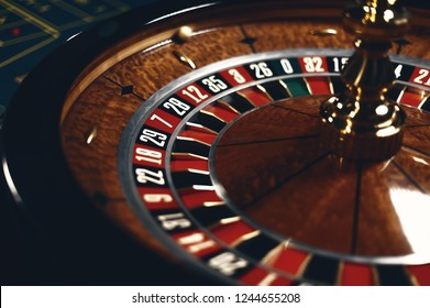 Roulette table in casino, with many games and slots, roulette wheel in the foreground. Golden and luxury light, casino interior. Gambling is the wagering of money or playing games of chance for money