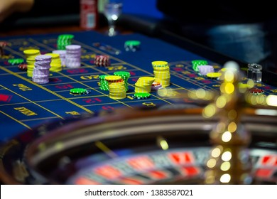 Roulette table with human hands putting down chips in casino. Roulette wheel in the foreground. Gamble game. Unrecognizable people.