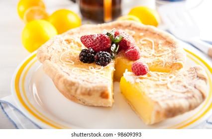 Round Artisan Lemon Tart Decorated with Berries and Powdered Sugar