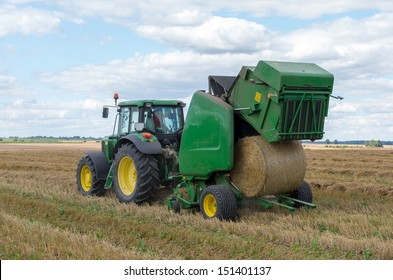 A round baler discharges a fresh wheat bale during harvesting.