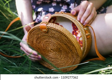 round bali bag. Hands open wickers bag on the natural backgraund