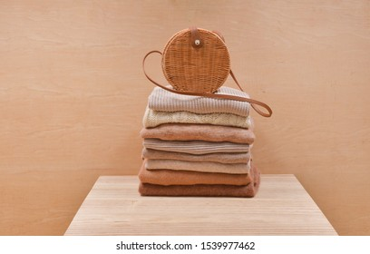 round bamboo handbag on Knitted wool sweaters. Pile of knitted winter clothe on wooden nbackground