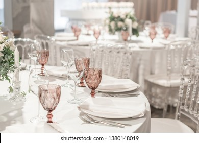 Round Banquet table served. Interior of restaurant for wedding dinner, ready for guests. Decorated with floral arrangement. Dishes, wine glasses and napkins. Catering concept.