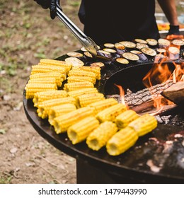 Round barbecue grill with open fire inside. Meals for the summer picnic are being prepared: corn, eggplant, bell pepper, kebab. Male hands in black gloves turn the food over with barbecue tongs