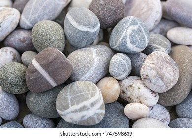 Round beach pebbles or smooth rocks with various colors and shapes of stones close up